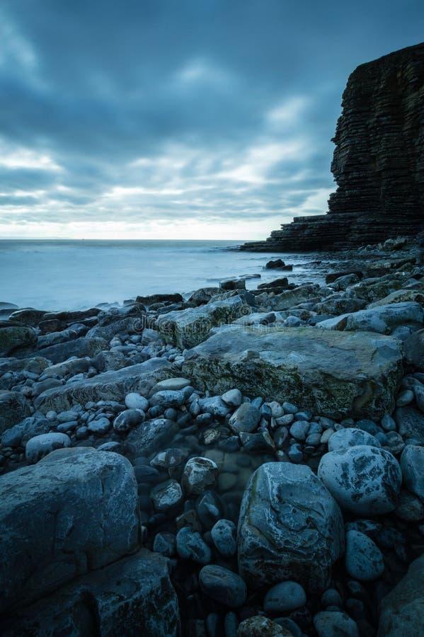 Nash Point at Dusk. Rocks on the coast next to the cliff face at Nash Point, Glamorgan coast, Wales royalty free stock photography