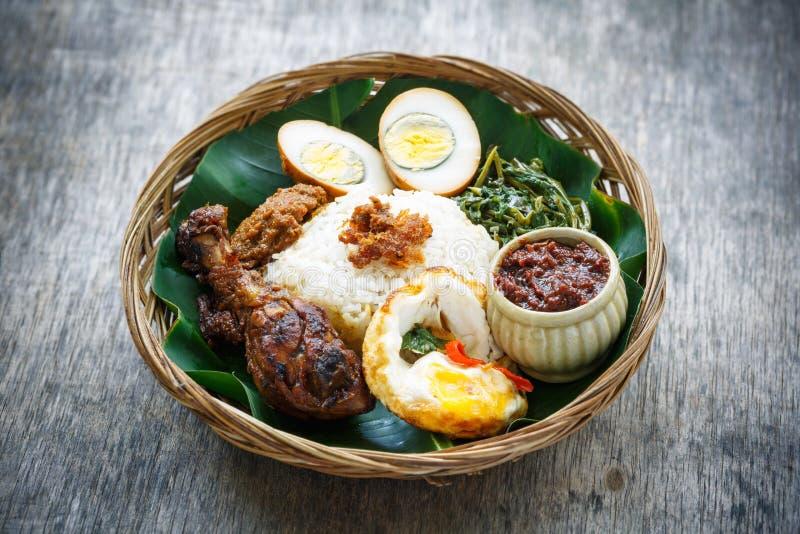 Nasi Ayam Penyet, индонезийский рис жареной курицы стоковое фото