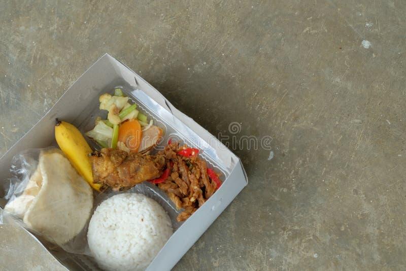 Nasi kotak eller lunchask Blandade ris med gr?nsaken och den fega fil?n arkivfoton