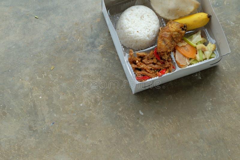 Nasi kotak eller lunchask Blandade ris med gr?nsaken och den fega fil?n arkivfoto