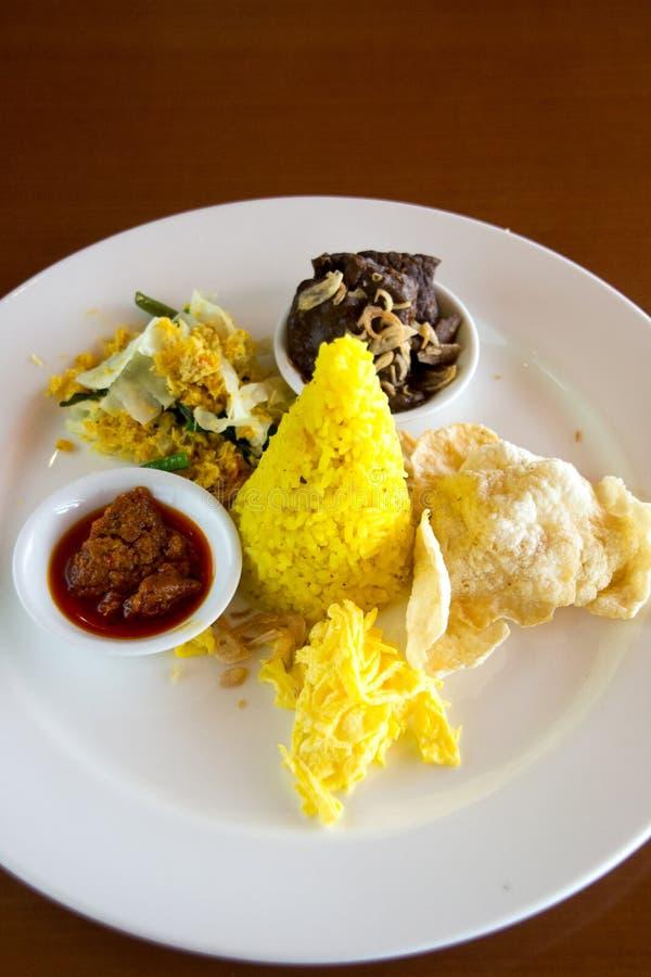 Nasi Kuning Indonesian amarela o arroz servido com carne assada, o ovo shredded, os vegetais, a salada do coco, o sambal caseiro  fotografia de stock