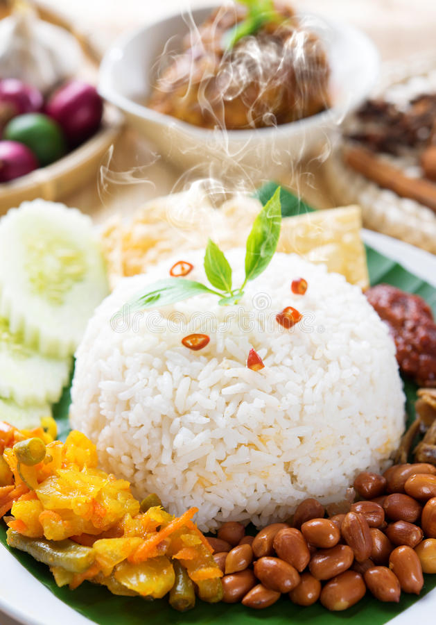 Nasi lemak with fresh hot steam. Nasi lemak traditional malaysia spicy rice dish, fresh cooked with hot steam. Served with belacan, ikan bilis, acar, peanuts and stock image