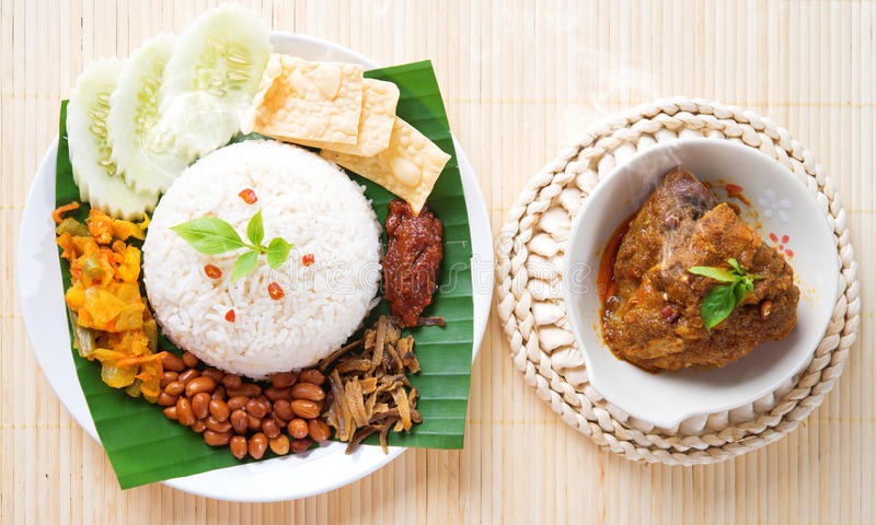 Nasi lemak hot and spicy. Nasi lemak is traditional malaysia spicy rice dish, fresh cooked with hot steam. Served with belacan, ikan bilis, acar, peanuts and stock photos