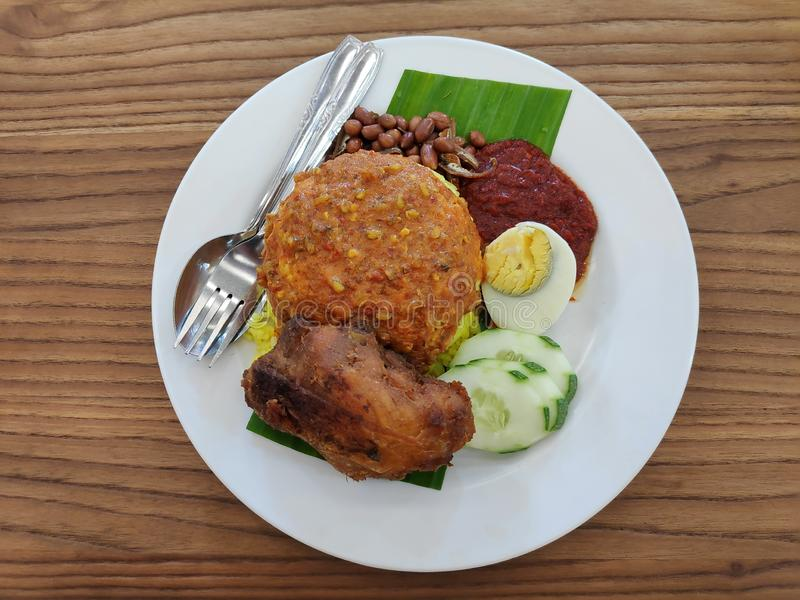 Nasi lemak serve with fried chicken,egg,anchovies,cucumber sliced,sambal and ground nuts royalty free stock image