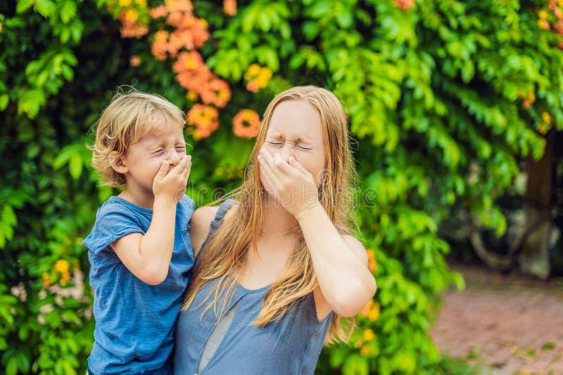 Naso di salto del figlio e della madre davanti all'albero di fioritura Concetto di allergia della primavera Allergie del ` s dei  immagine stock libera da diritti