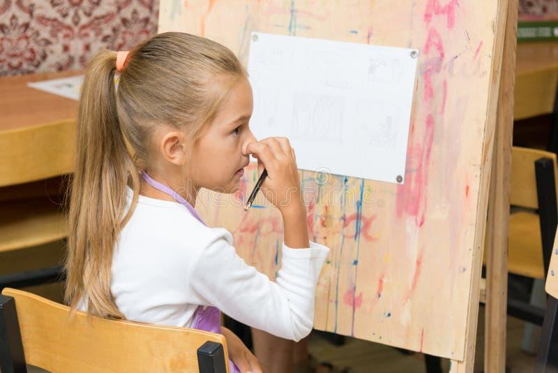 Naso di scratch della ragazza che ascolta con attenzione l'insegnante alla lezione del disegno immagini stock