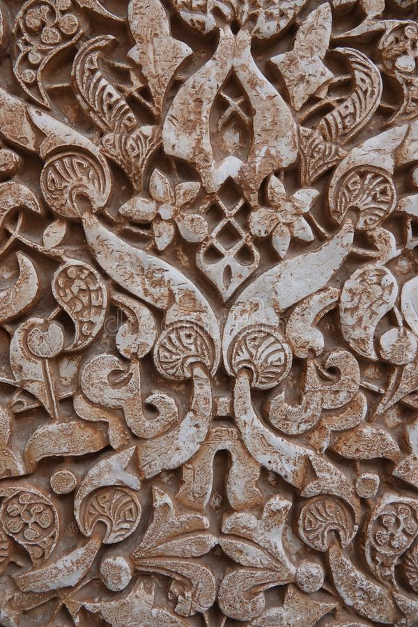 Nasrid palace arabesque ornaments at the Alhambra in Granada, Andalusia. Decoration of arabesque ornaments in the Palacio Arab at the Court of the Myrtles of the stock image