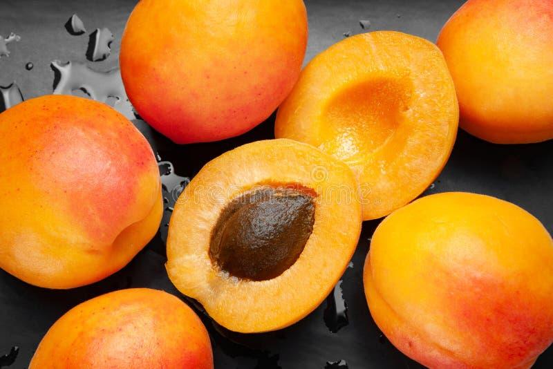 Nass Aprikosen auf einem nass dunklen Hintergrund Frische saftige rötliche Aprikosen auf einer dunklen Lehmplatte mit Tropfen ges stockfotos