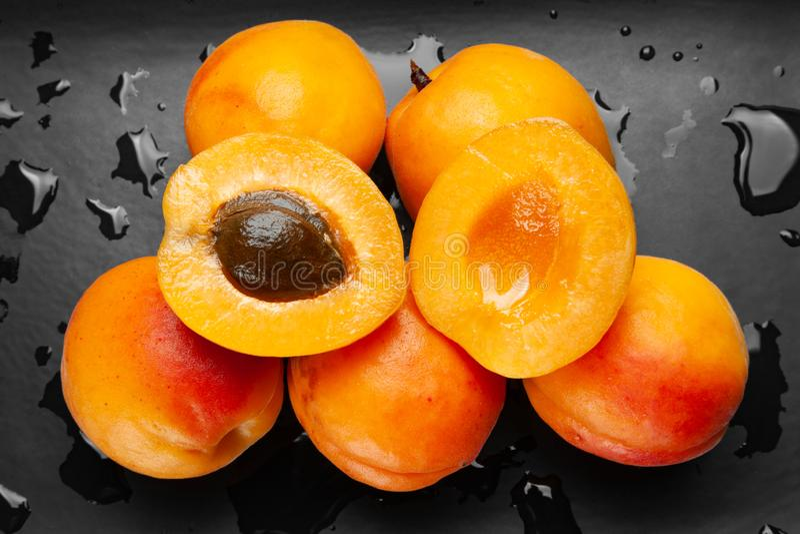 Nass Aprikosen auf einem nass dunklen Hintergrund Frische saftige rötliche Aprikosen auf einer dunklen Lehmplatte mit Tropfen ges stockfotografie