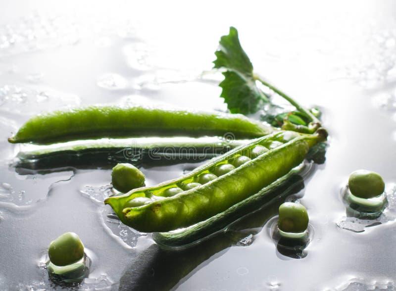 Nass grüne Erbsen auf Tafelwasserfront-Gemüsemakro lizenzfreies stockbild