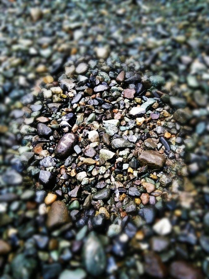 nass kleine Kieselwellenzusammenstellung auf dem Strand stockfotos