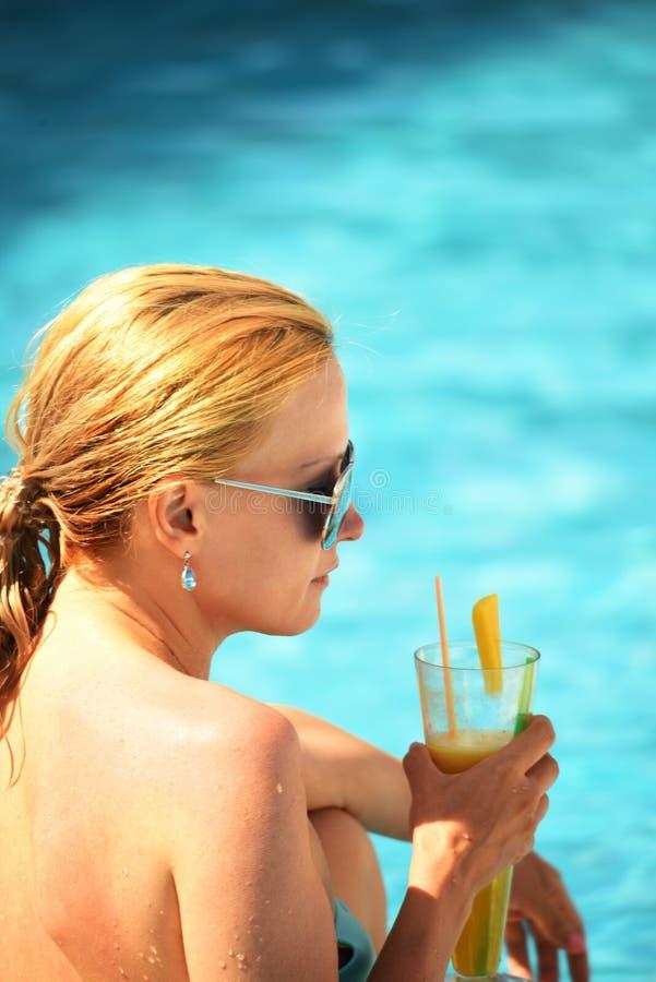 Nass Mädchen tauchte von der Wassergetränkorange auf, die durch das Pool frisch ist stockfotos