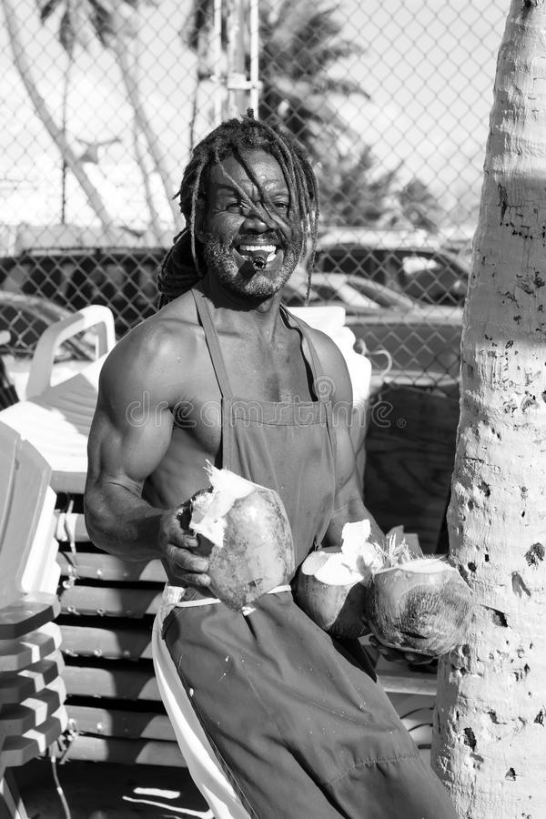 Happy muscular afroamerican man with smile break big raw coconut royalty free stock photo