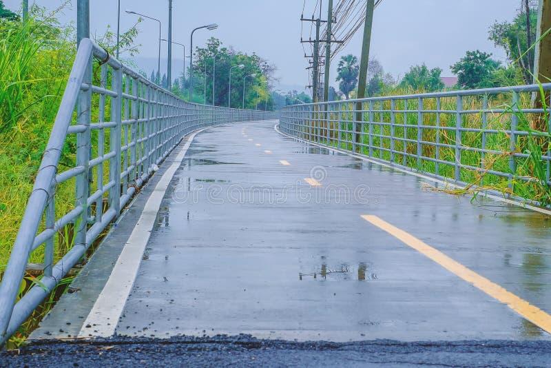 Nasse Straße nach Regen der die gelbe Linie, zum in zwei Wege unterzuteilen stockbilder