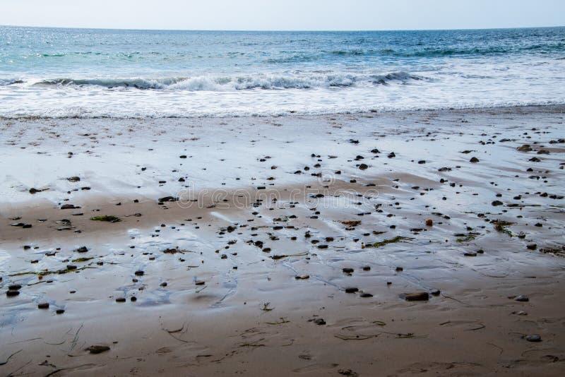 Nasser Sand des felsigen Strandes mit vielen kleinen Felsen Blauer Ozean mit kleinen Wellen und Horizont im Hintergrund lizenzfreie stockfotografie