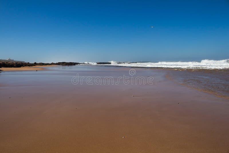 Nasser Sand eines Strandes während einer Flut Weiße Spitzen der Wellen auf dem Recht, schwarze Felsen auf dem links Heller blauer lizenzfreies stockbild