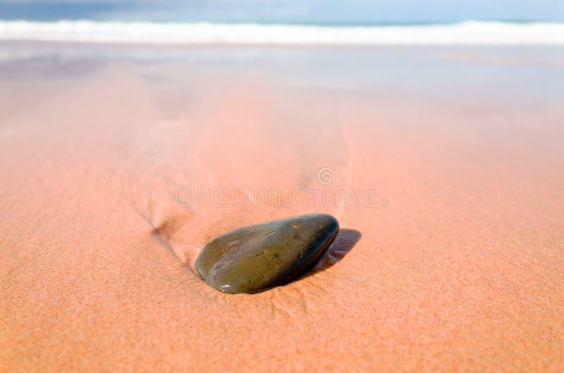 Nasser Stein auf Strandsand mit Wellen und blauem Meer lizenzfreie stockfotos