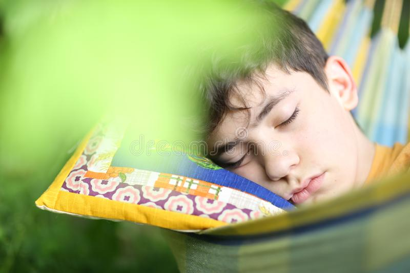 Nastolatek chłopiec odpoczynkowy sen z książką w hamaku na lato zieleni ogródzie obraz royalty free