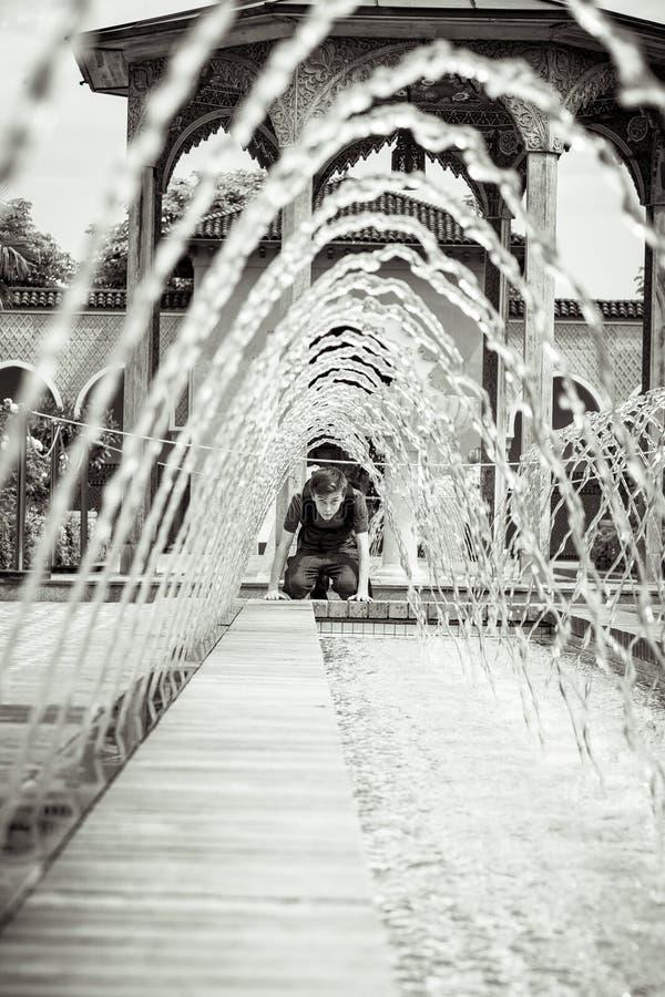 Nastolatek chłopiec patrzeje przez fontanny zdjęcie stock