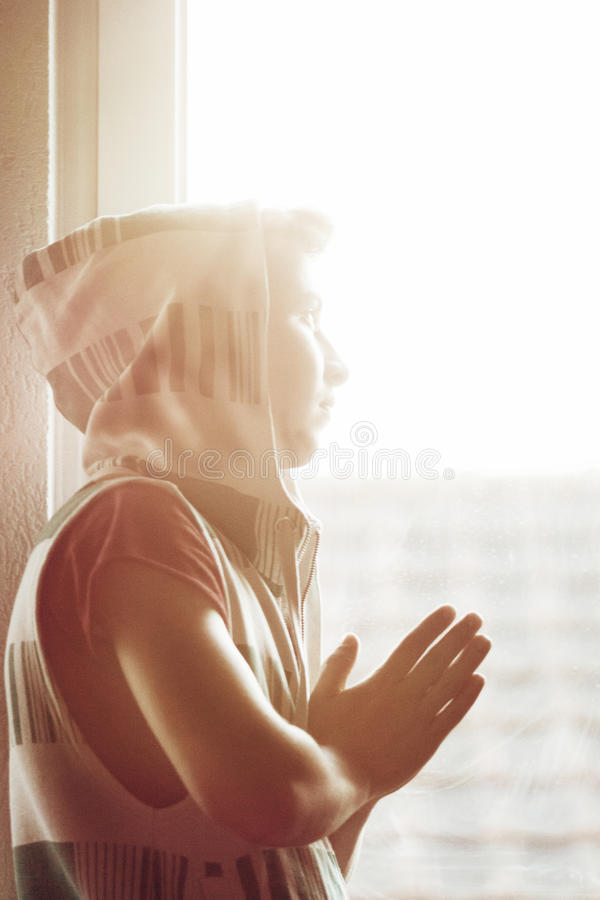 Nastolatek chłopiec patrzeje słońce z hoodie i ono modli się zdjęcie stock
