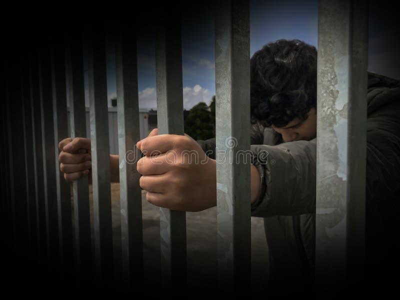 Nastolatek chłopiec wręcza trzymać silnych stalowych pręt Imigranta i uchodźcy kryzys Dramatycznej granicy płotowy lub więźniarsk zdjęcia stock