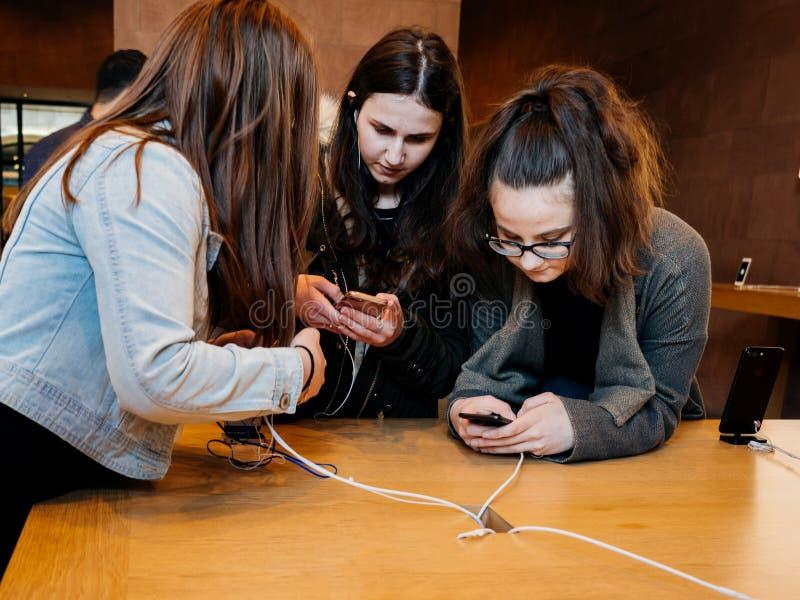 Nastolatek dziewczyn przyjaciele bada opóźnionego iphone w Apple Store zdjęcie stock