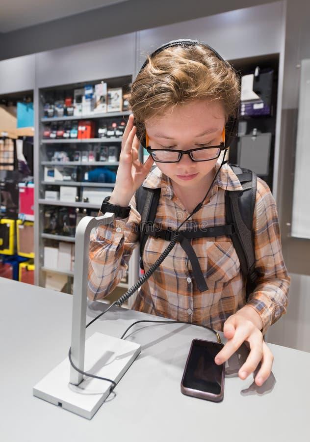 Nastolatek dziewczyna bada hełmofony w sklepie obrazy stock