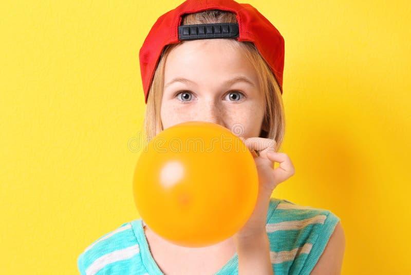 Nastolatek dziewczyna w czerwonym kapeluszowym pompowanie balonie na żółtym tle zdjęcia royalty free