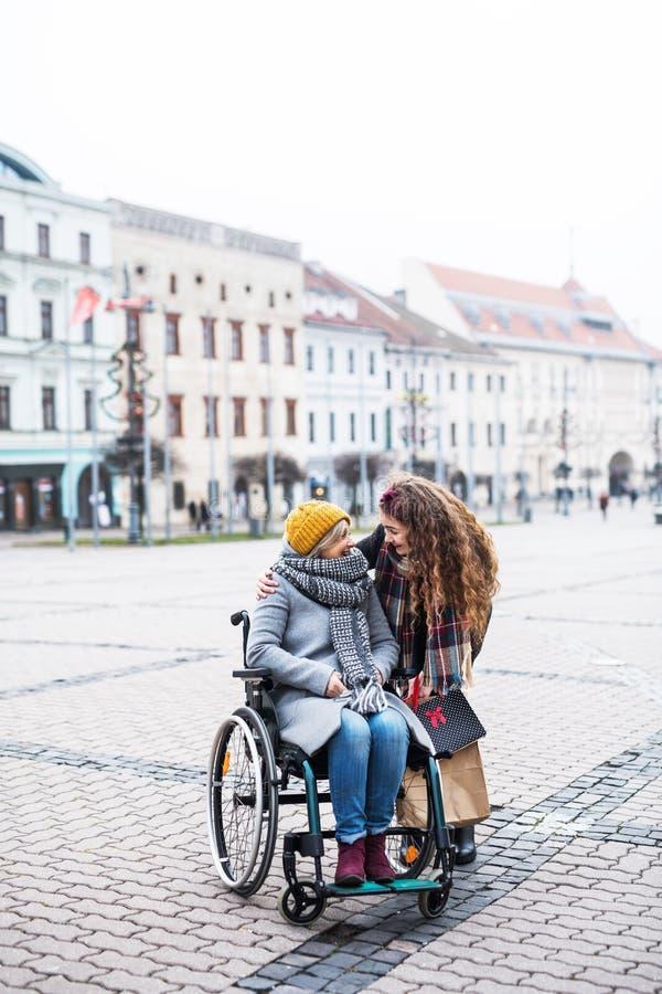 Nastolatek dziewczyna z niepełnosprawną babcią w wózku inwalidzkim outdoors na ulicie w zimie zdjęcia royalty free