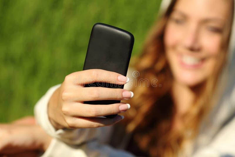 Nastolatek dziewczyny ręka używać mądrze telefon z jej twarzą w tle zdjęcie royalty free