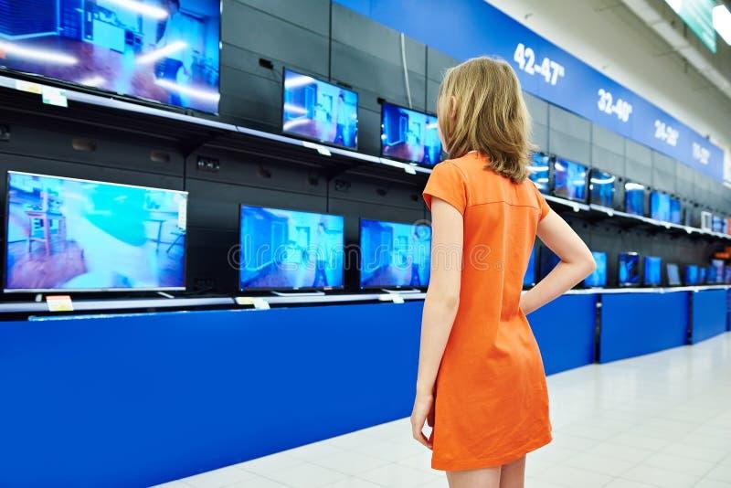 Nastolatek dziewczyny spojrzenia przy LCD TVs w sklepie zdjęcie stock