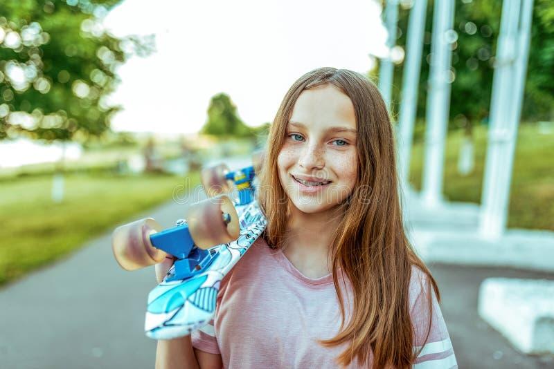 Nastolatek dziewczyny 10-12 szczęśliwy ono uśmiecha się w piegach i z brasami na zębach, w lecie w mieście na ramieniu a, zdjęcie royalty free