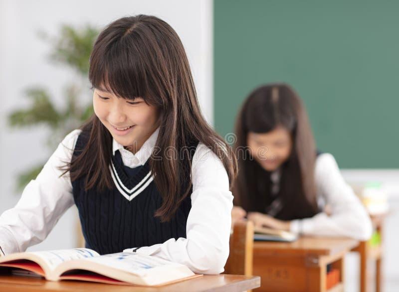 Nastolatek dziewczyny ucznia studiowanie w sala lekcyjnej fotografia royalty free