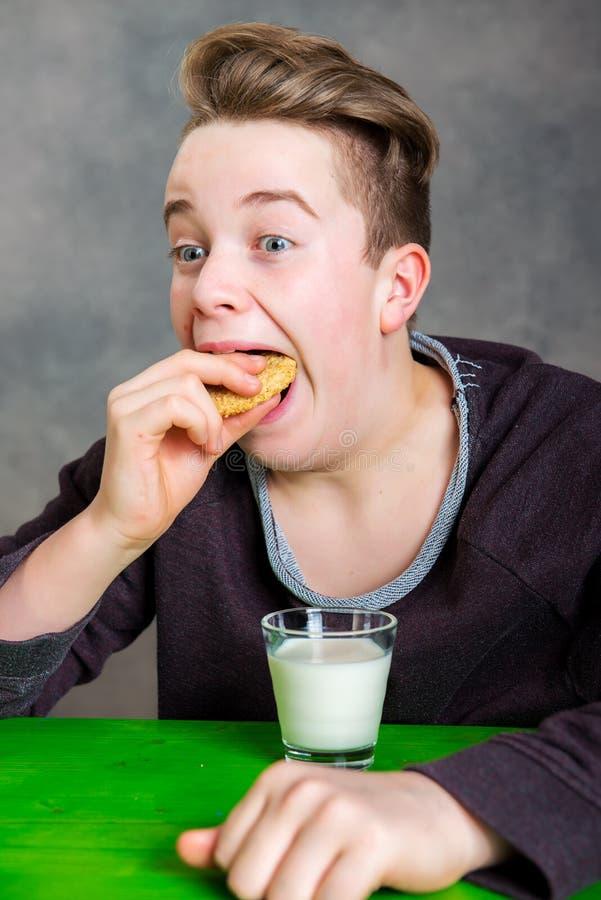 Nastolatek je grabby ciastka i napoju mleko zdjęcie stock