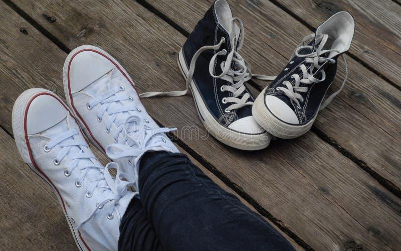 Nastolatek jest ubranym biel kuje obsiadanie obok czarnych snickers, wyborowy pojęcie zdjęcia stock