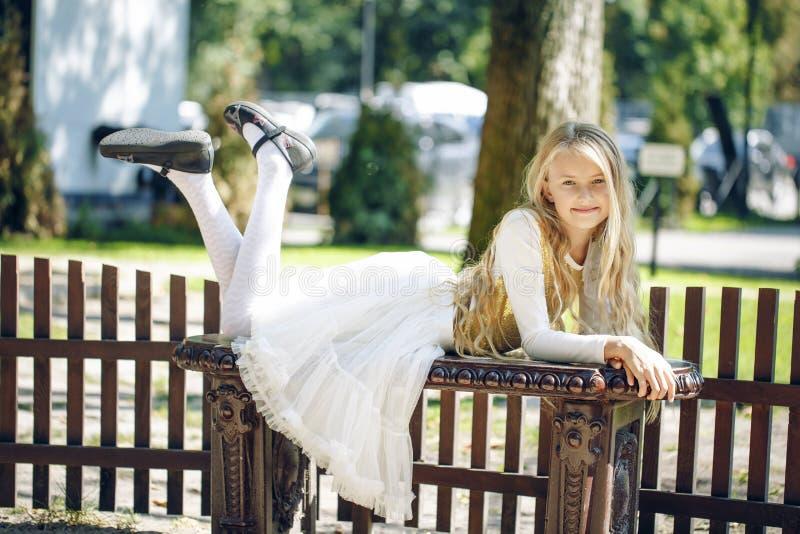 Nastolatek młodej dziewczyny lying on the beach na ławce w parku zdjęcia royalty free