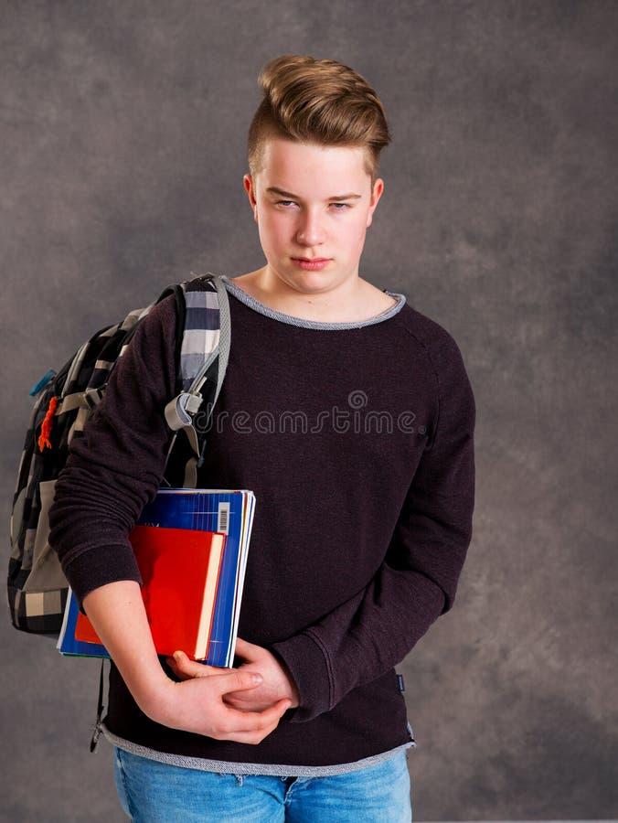 Nastolatek patrzeje gniewny z satchel i książki zdjęcia stock