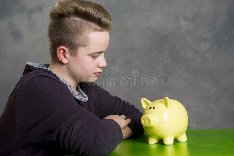 Nastolatek patrzeje piggybank fotografia royalty free