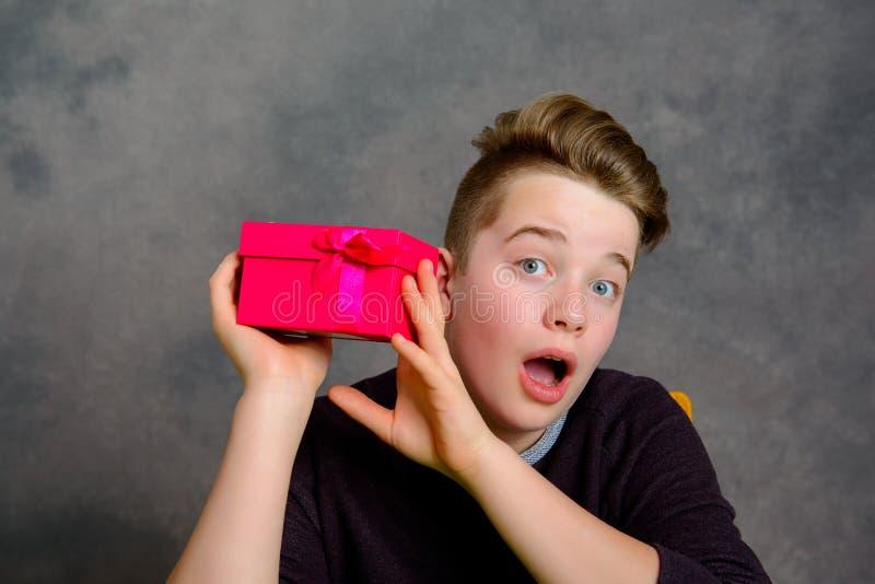 Nastolatek patrzeje zaskakujący z czerwonym prezenta pudełkiem obraz royalty free