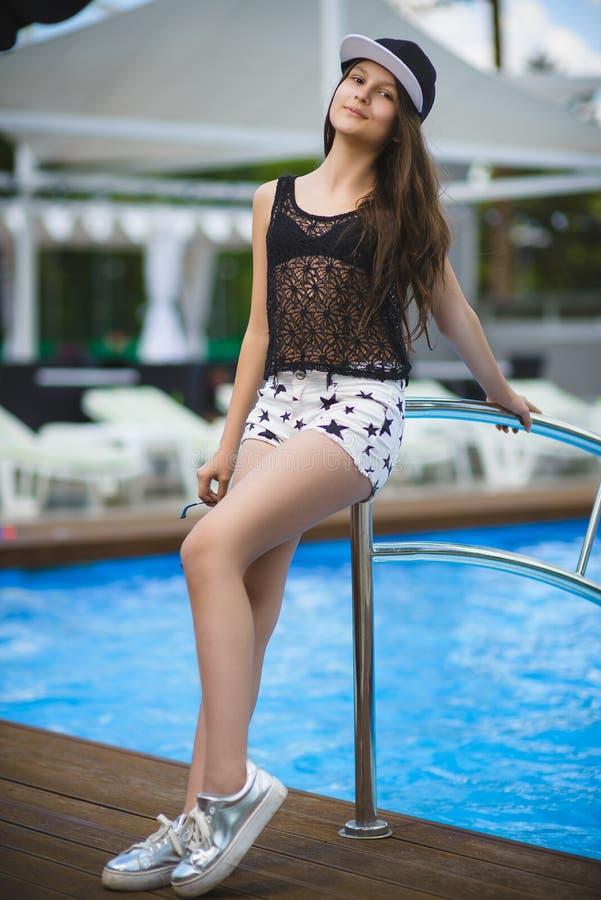 Nastolatek piękna dziewczyna siedzi blisko basenu plenerowego zdjęcia stock
