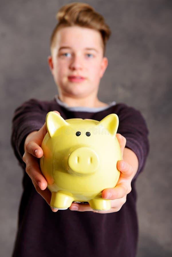 Nastolatek pokazuje piggybank zdjęcie stock