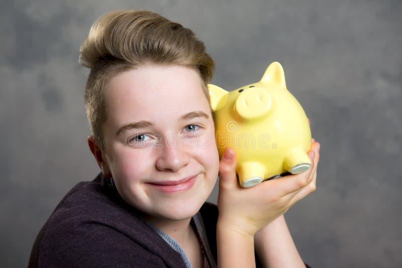Nastolatek pokazuje piggybank zdjęcia stock