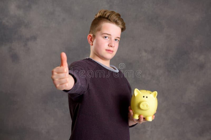 Nastolatek pokazuje piggybank i kciuk up obrazy stock