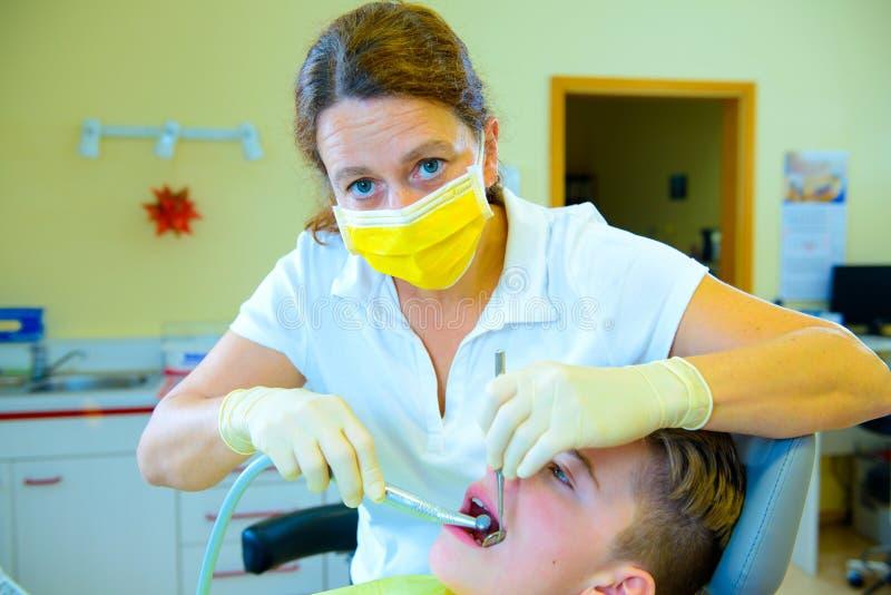 Nastolatek przy żeńską dentysty ` s operacją obraz royalty free