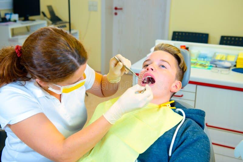 Nastolatek przy żeńską dentysty ` s operacją fotografia stock