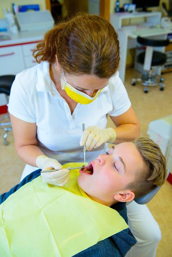 Nastolatek przy żeńską dentysty ` s operacją obraz stock