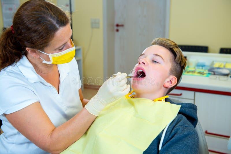 Nastolatek przy żeńską dentysty ` s operacją zdjęcie royalty free