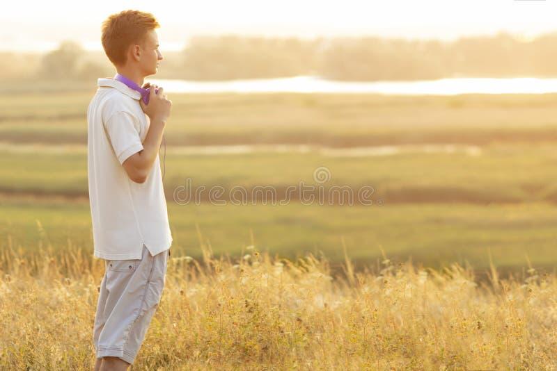 Nastolatek słucha muzyka na naturze, twarz profil patrzeje w odległości młody człowiek i cieszyć się piękny w hełmofonach, fotografia stock
