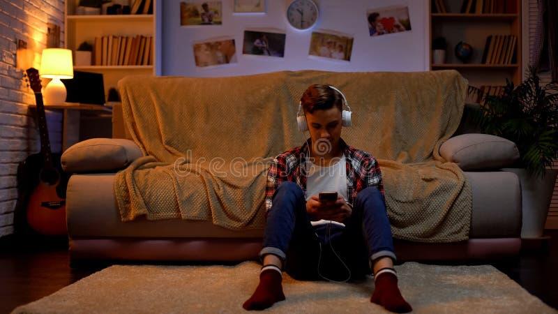 Nastolatek s?ucha muzyka w s?uchawkach, gaw?dzi z przyjaci??mi na telefonie, gad?et zdjęcie stock