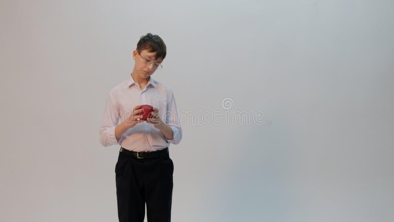 Nastolatek trzyma czerwonego jabłka w szkłach Śmieszna emocja w postaci znakomitego ucznia który patrzeje jak nieudacznik Uczniow zdjęcie royalty free